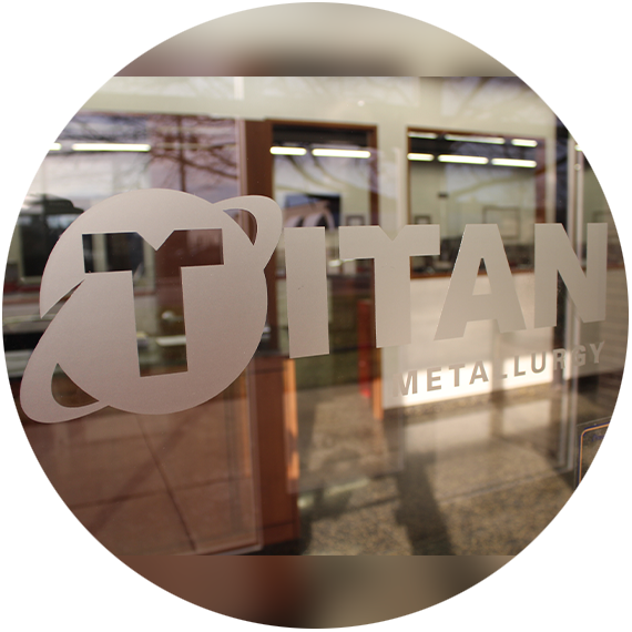 Titan Metallurgy logo etched on glass.