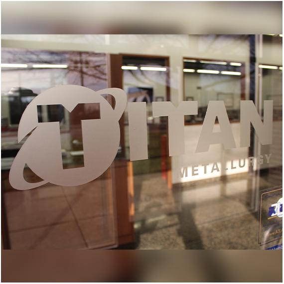 Titan Metallurgy logo etched on glass.